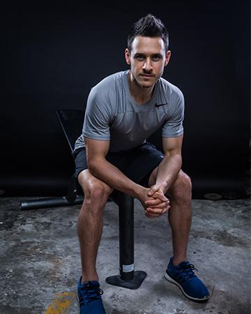 Aidan Sydney fitness model seated on gym bench