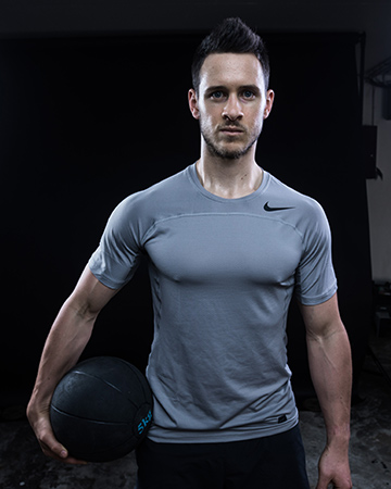 Aidan male Sydney fitness model holding medicine ball