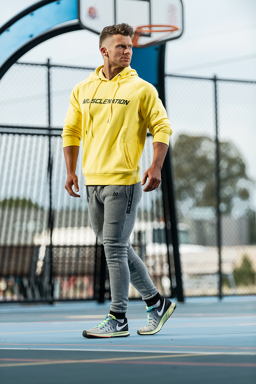 Alan Melbourne's new male model wearing grey fitted track pants with bottoms with a yellow hoody walking on basketball court