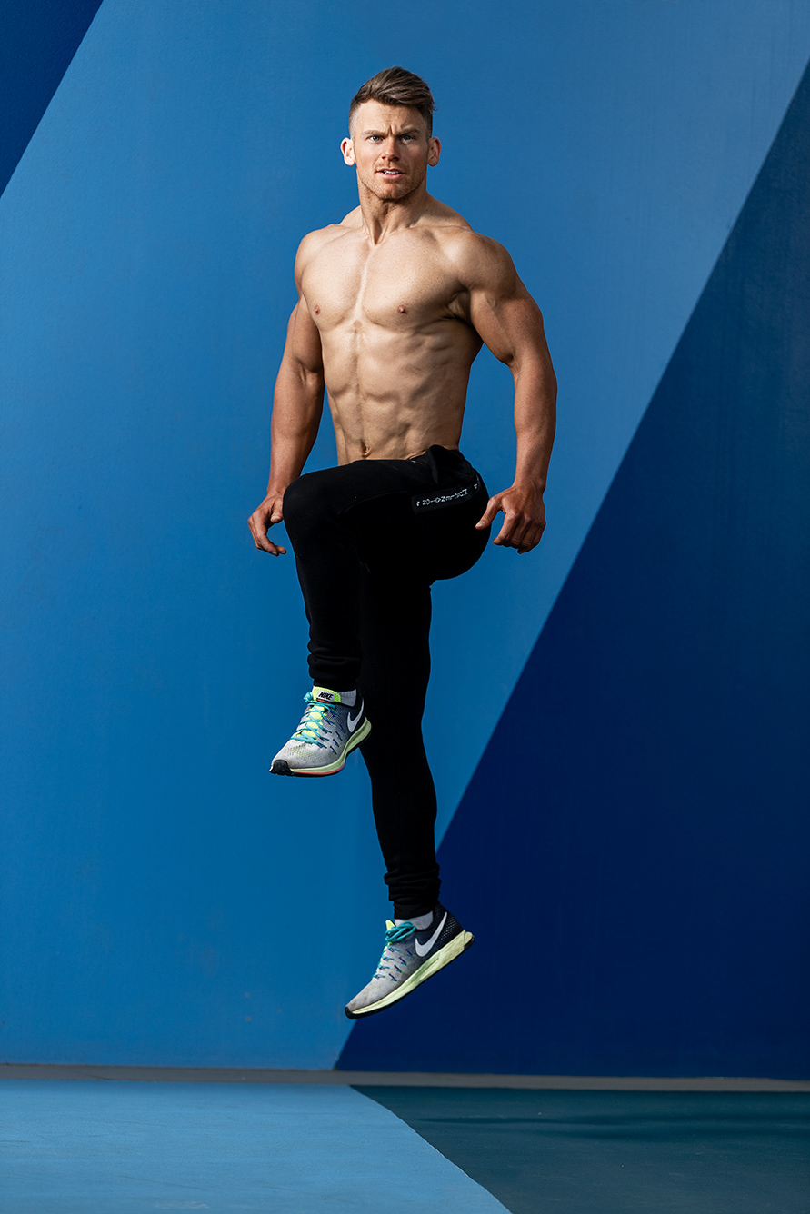 Alan jumping in front of a two-tone blue wall