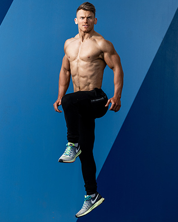 Alan jumping with one knee tucked to his chest, against a blue wall topless
