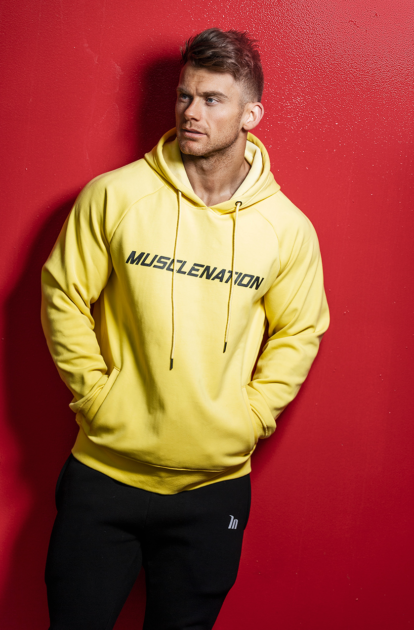 Alan leaning against a red wall wearing a yellow muscle nation hoody