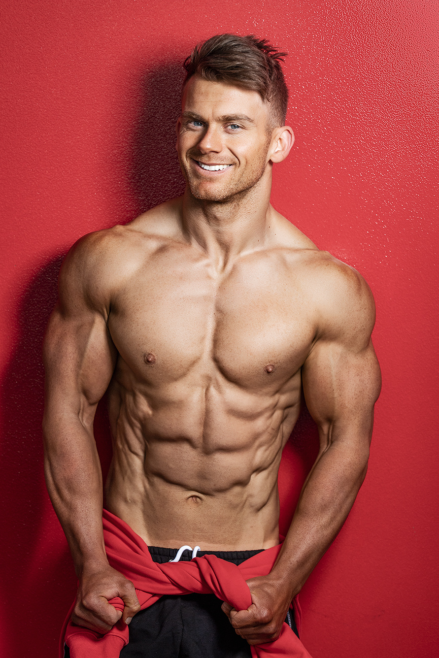Alan smiling whist leaning against a red wall pulling on his hoody around his waist flexing his triceps
