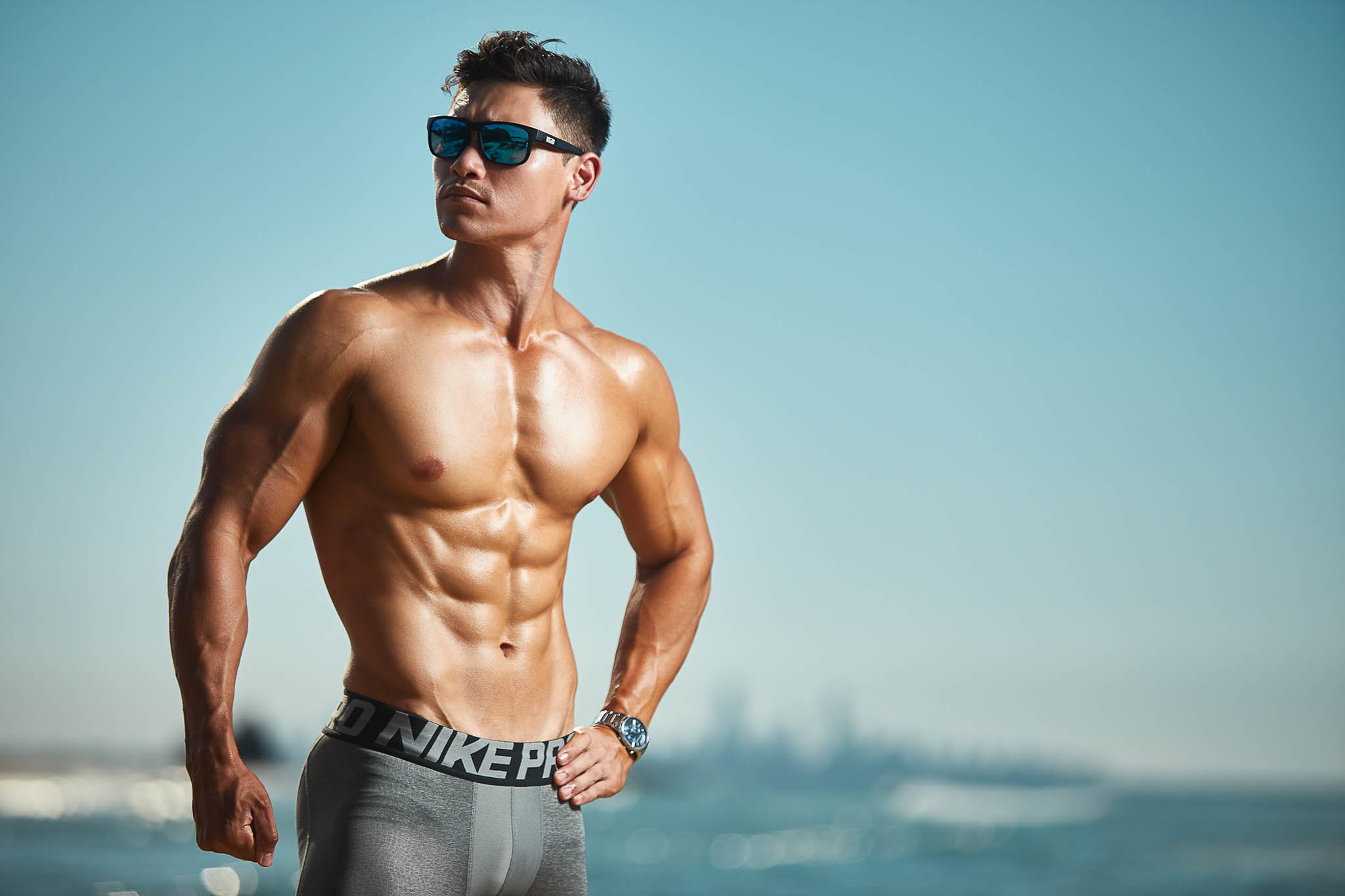 Andrew Mc at the beach flexing his toned physique wearing sunglasses