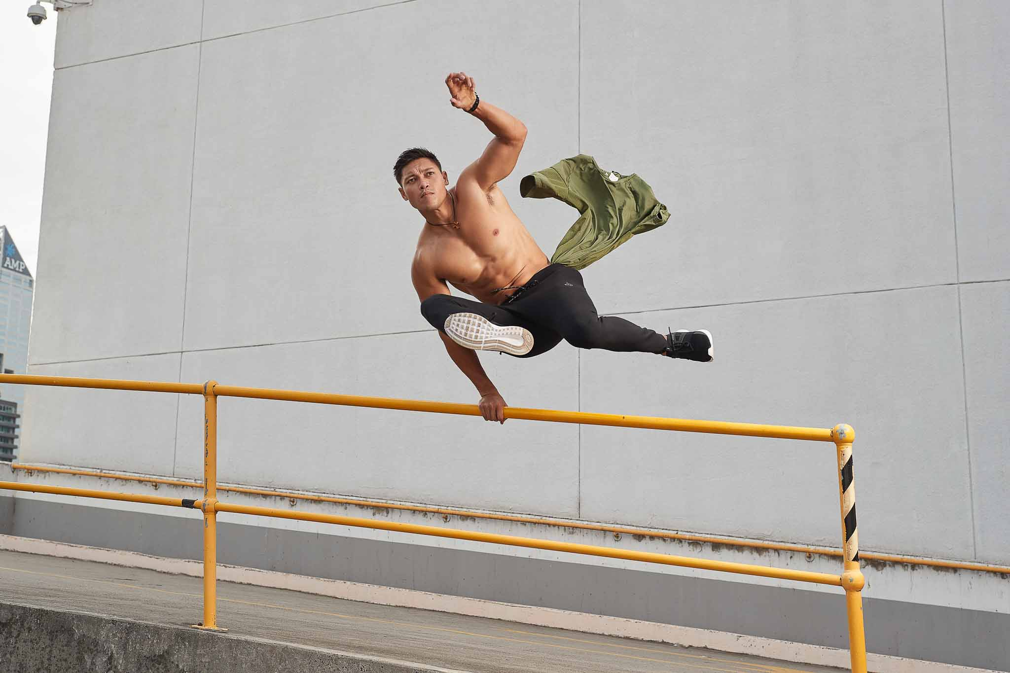 Andrew Mc jumping over a yellow metal rail topless