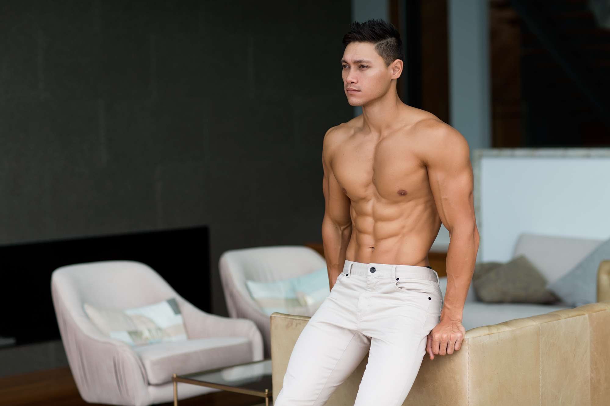 Andrew Mc seated on armchair wearing cream slacks, topless flexing his abdominals