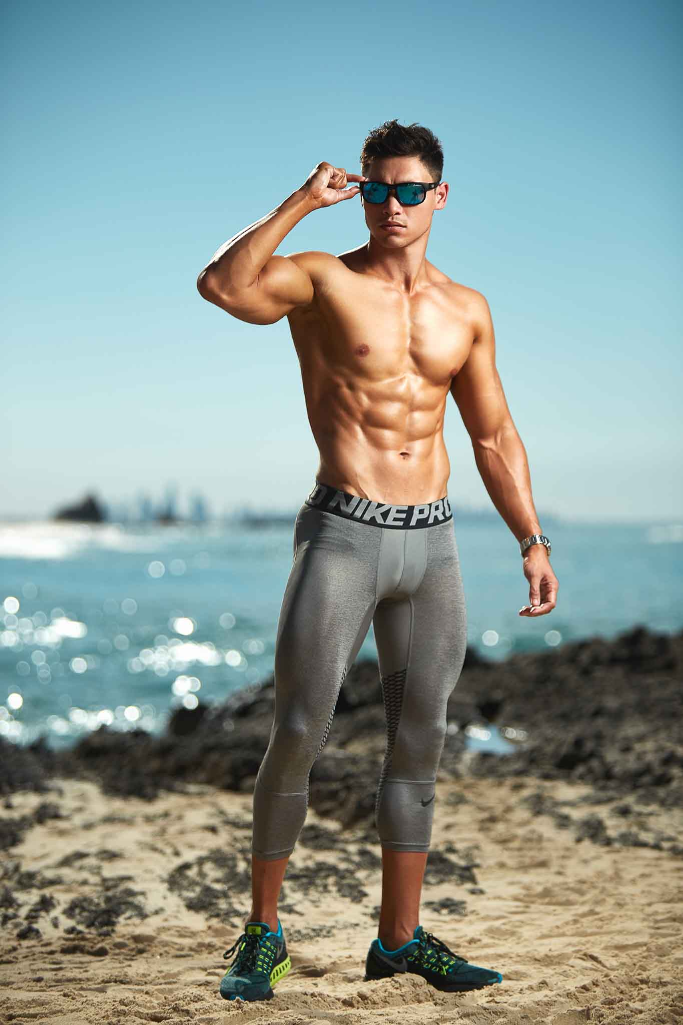 Andrew Mc standing on Queensland beach wearing sunglasses and Nike pro grey skins