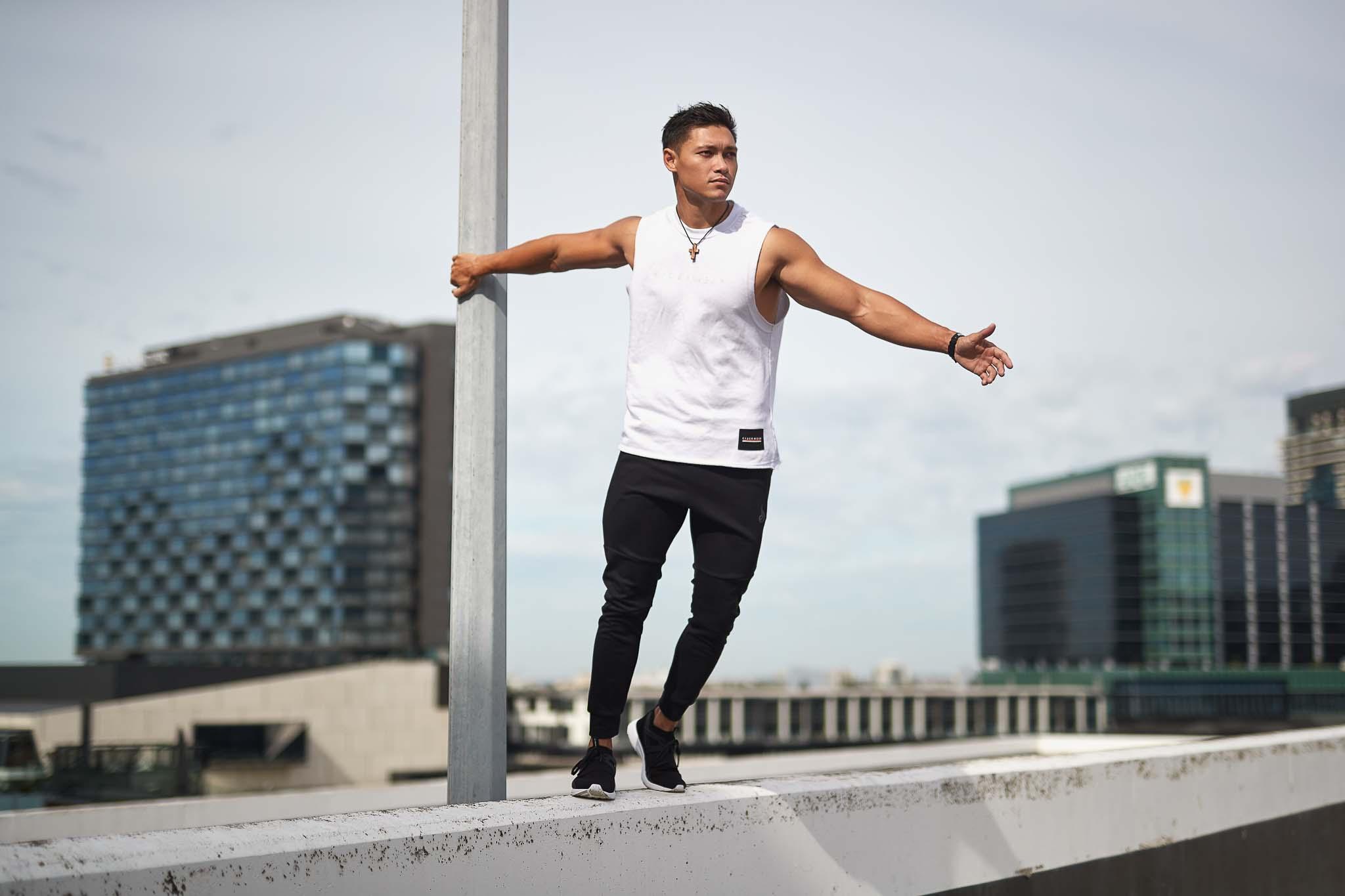 Andrew Mc standing on car park ledge holding metal pole