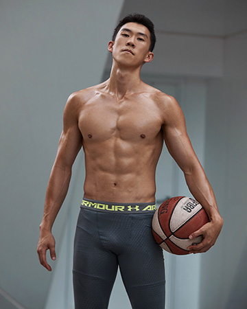 Andrew standing in a strong pose with basketball topless