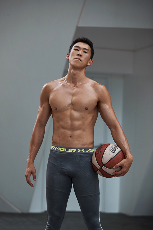 Andrew topless wearing underarmour skins while holding basketball