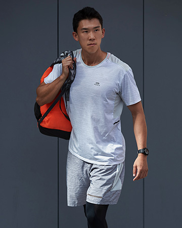 Andrew walking with sports bag over right shoulder