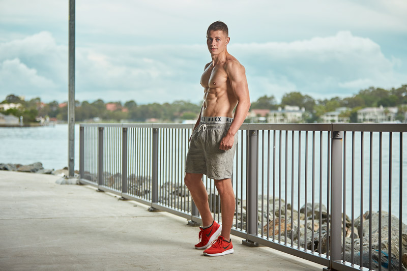 Angus Queensland male athletic model posing topless on boardwalk