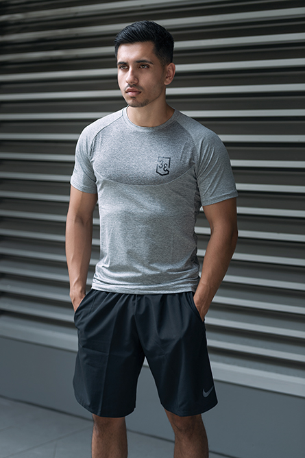 Ben P male fitness model wearing grey fitted top standing in front of metal wall