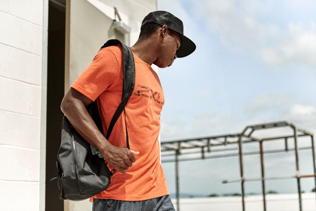 Bibby entering an open air gymnasium holding 2XU bag wearing a orange 2XU vibrant T-shirt