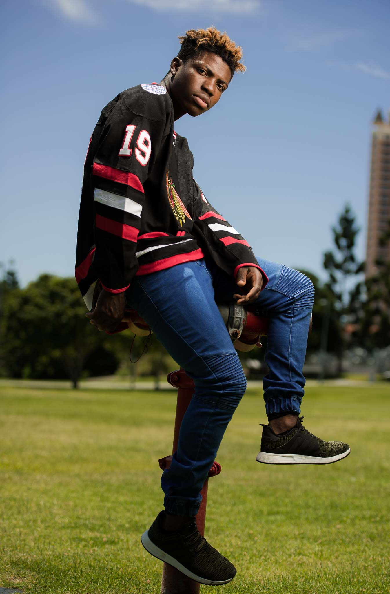 Bibby seated on top of a fire hydrant wearing jeans and an American hockey sweater