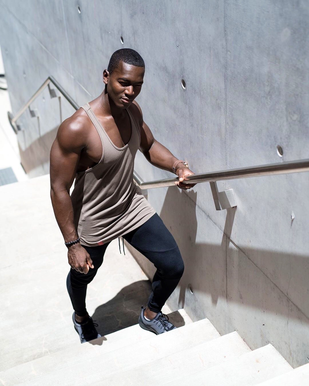 Bobby T holding onto a handrail during fitness shoot