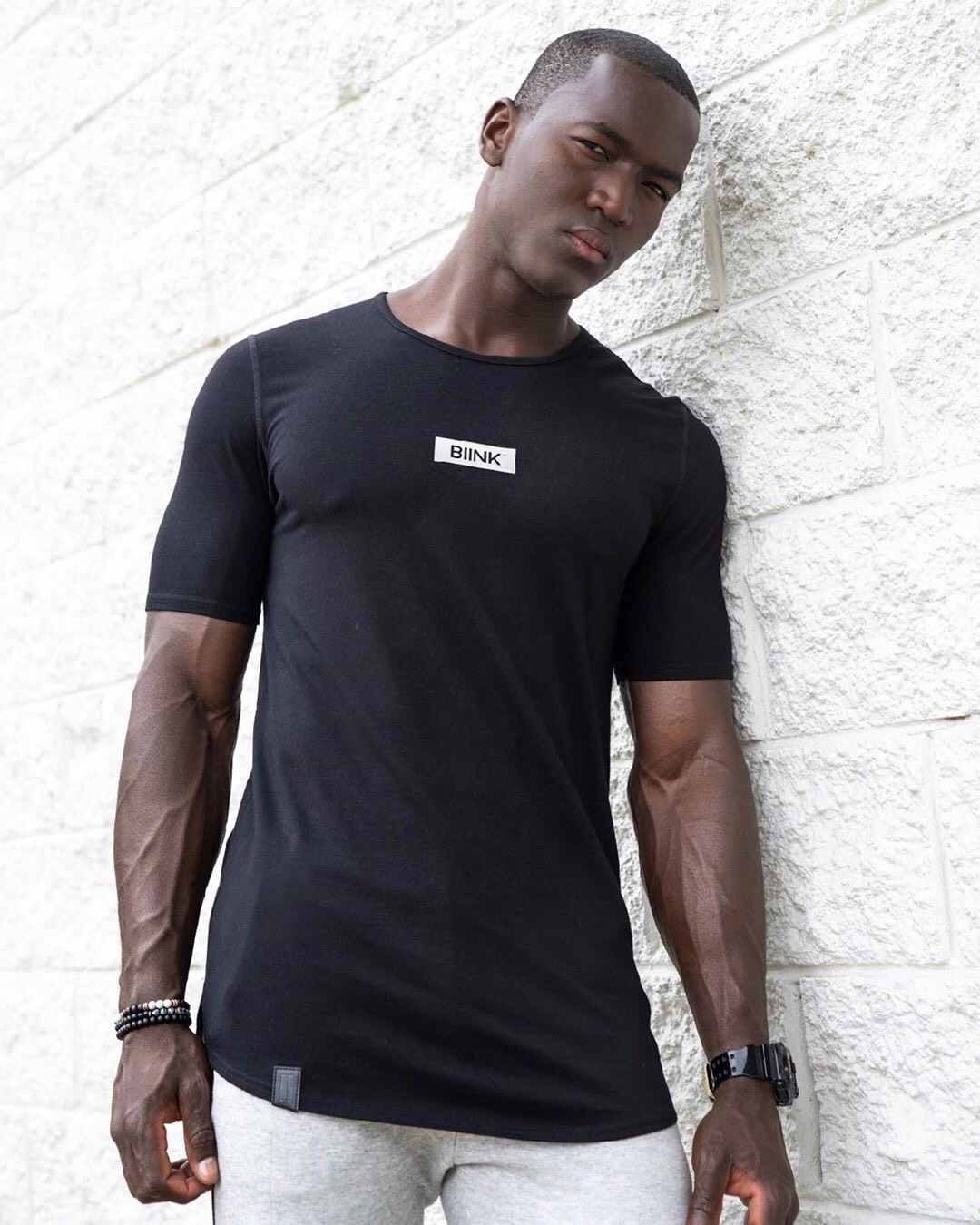 Bobby T leaning against a white brick wall wearing a black BINK fitness top