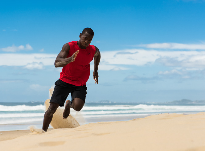 Bobby T running across the hot sand in black Nike shorts and a fitted Nike red top