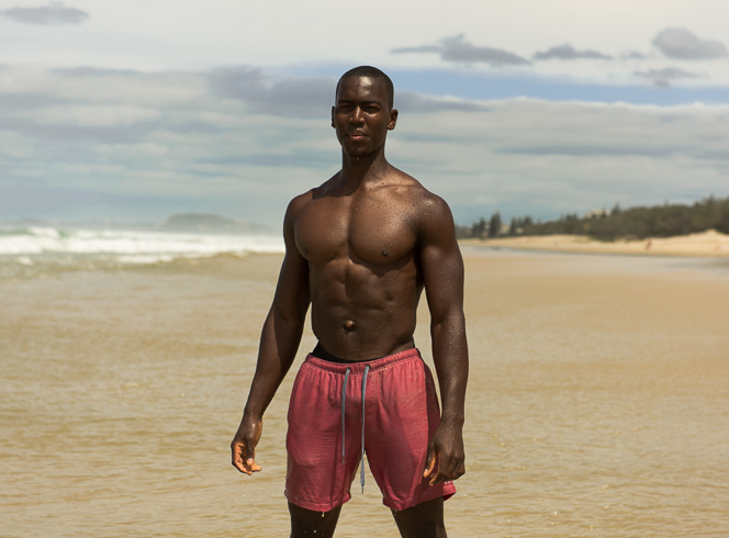 Bobby T standing at the beach with no top on