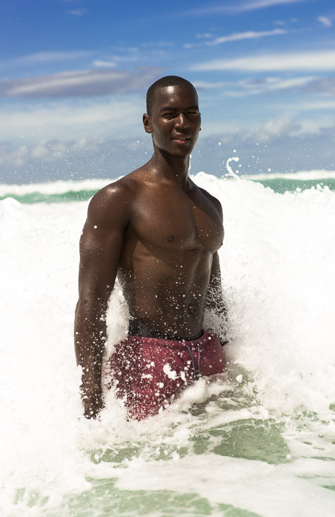Bobby T standing in the surf as the water crashes over him