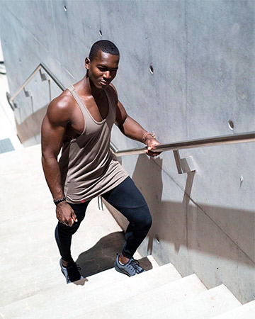 Bobby T wearing tight singlet looking up the staircase
