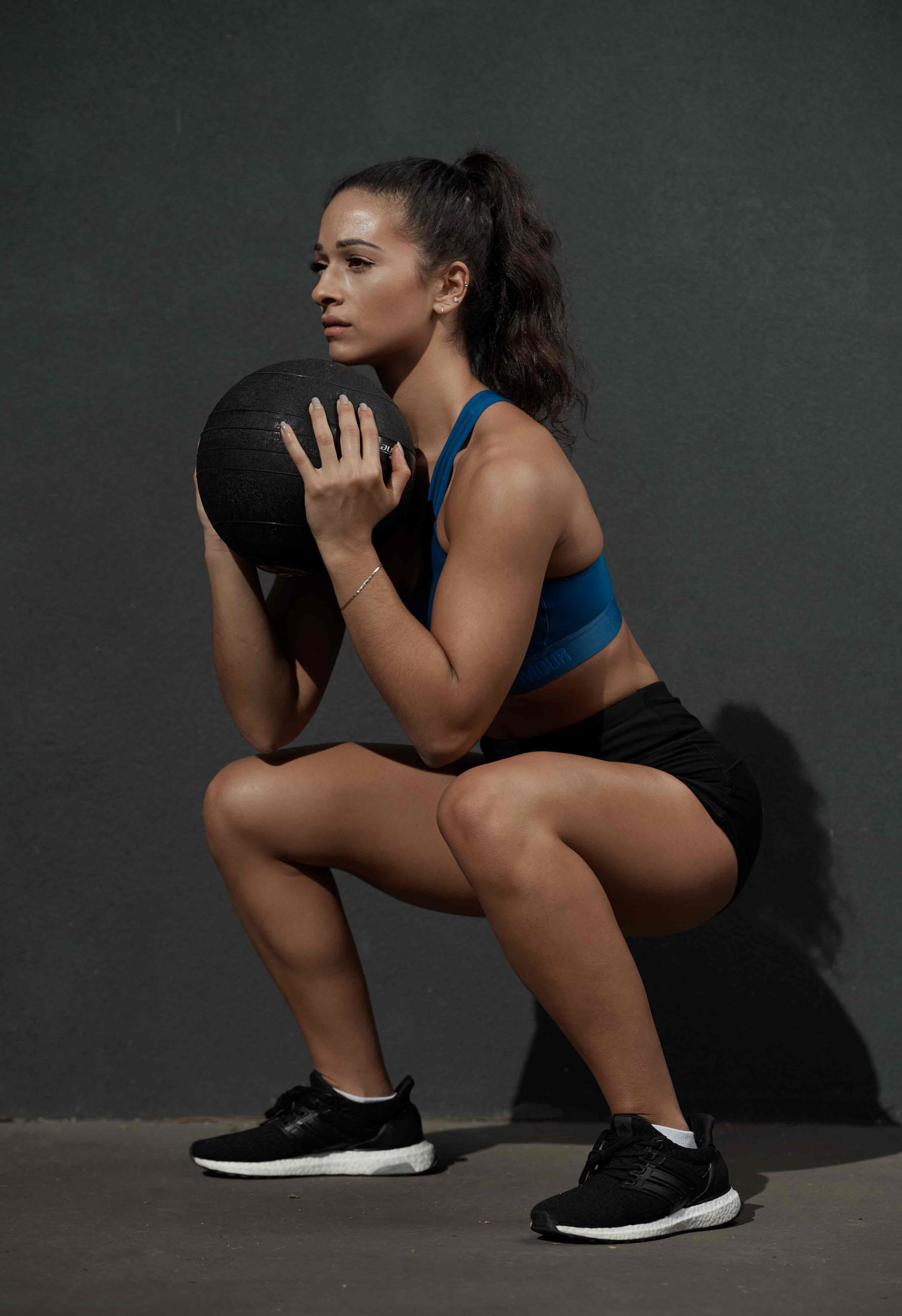 Brenice squatting with a medicine ball