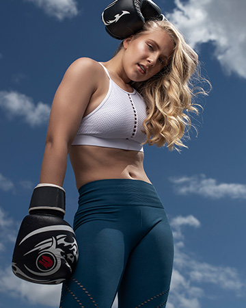 Caitlin posing with boxing gloves in sports wear