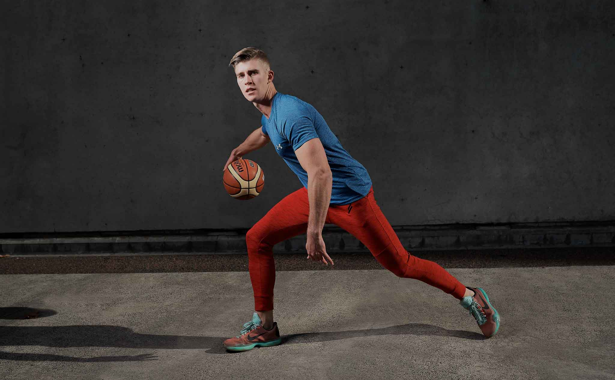 Callum dribbling a basketball wearing red jog pants and a blue loose top in front of a concrete wall