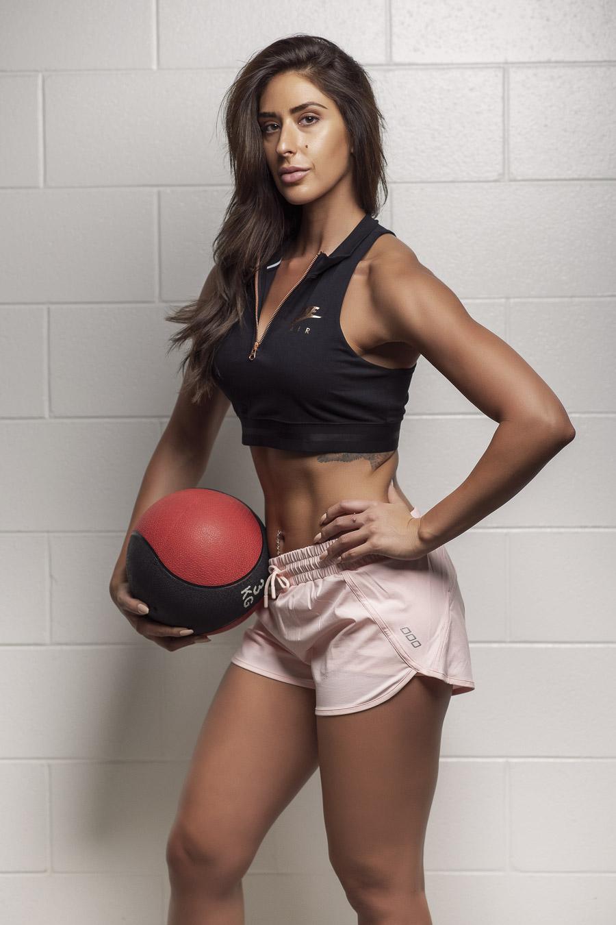 Cassie Adelaides latest female fitness sensation holding medicine ball during fitness shoot