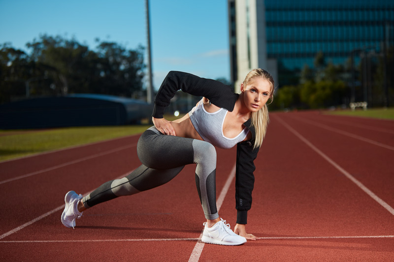 Centelle stretching on Gold Coast Griffiths athletic track