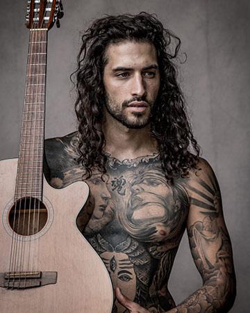 Christian C Byron Bay fitness model with full body art holding guitar