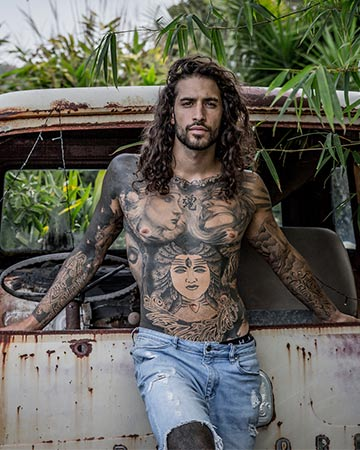 Christian C Byron Bay tattooed fitness model seated in the back of a Combi van