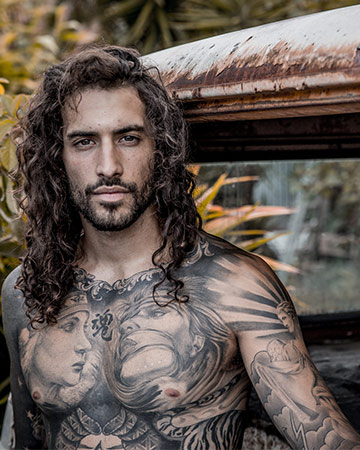 Christian C full body tattooed fitness model posing in the back of a Combi van in Byron Bay
