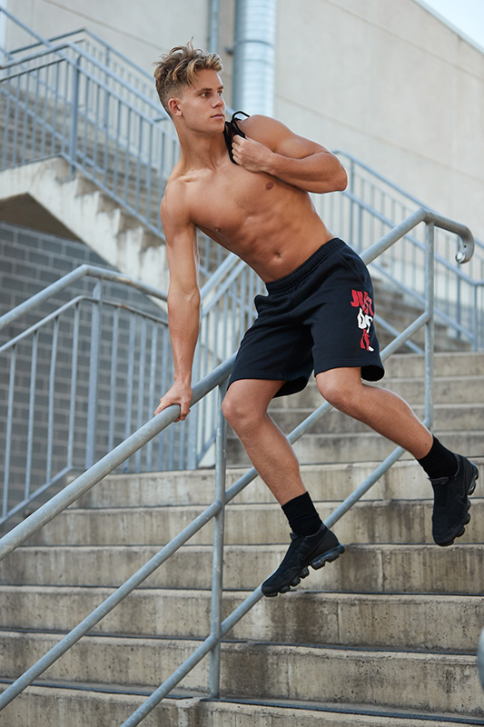 Connor bounding down a flight of stairs topless