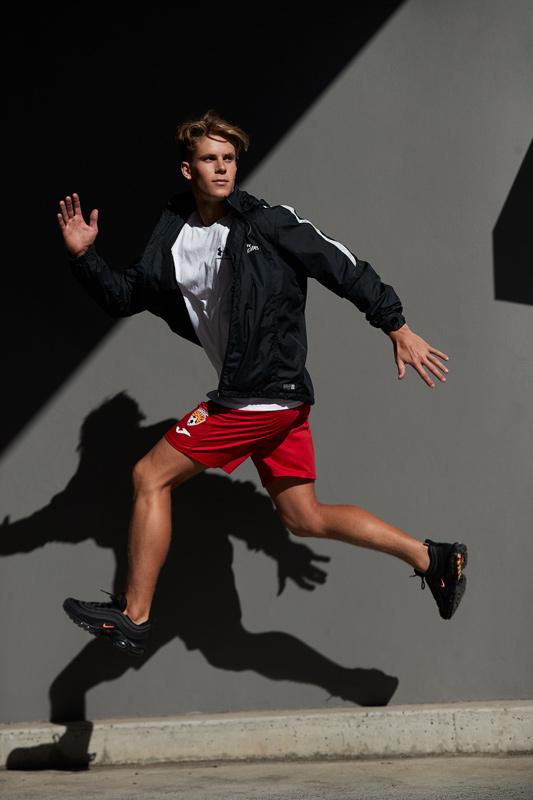 Connor jumping wearing Nike garments against dark grey wall