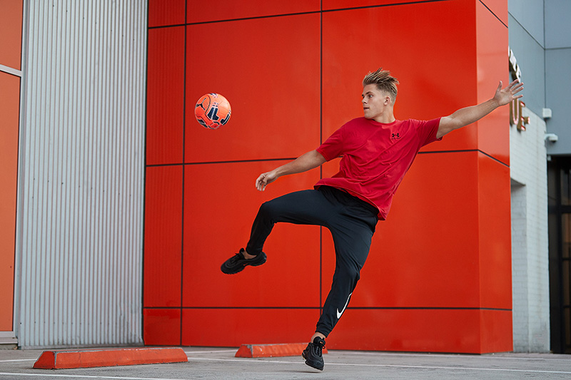 Connor kicking a football against a red background