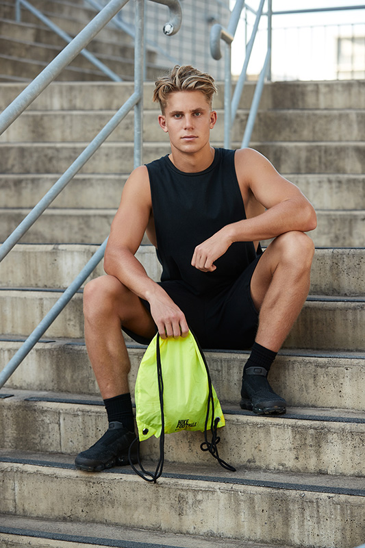 Connor seated on a flight of stairs holding a Nike training bag