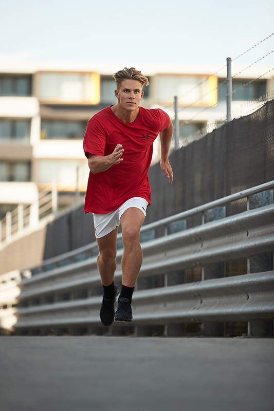 Connor sprinting on a rooftop wearing Nike T-shirt and black Nike shorts
