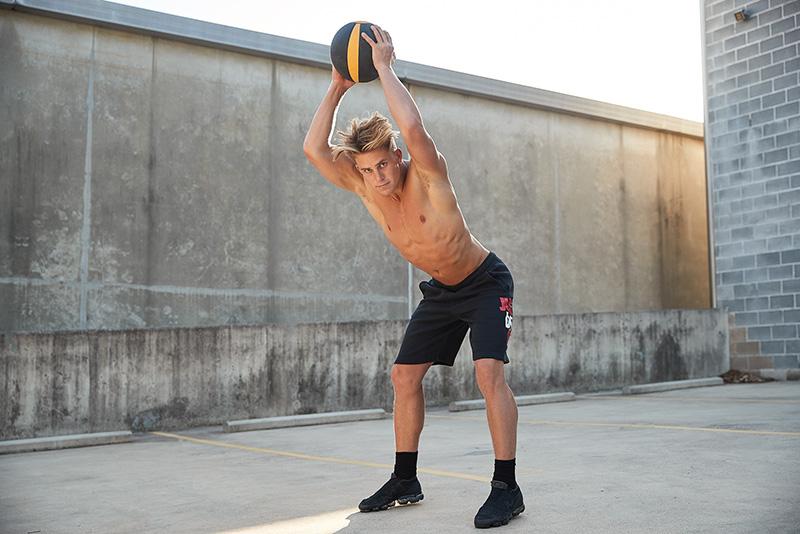 Connor topless wearing Nike shorts slamming a medicine ball