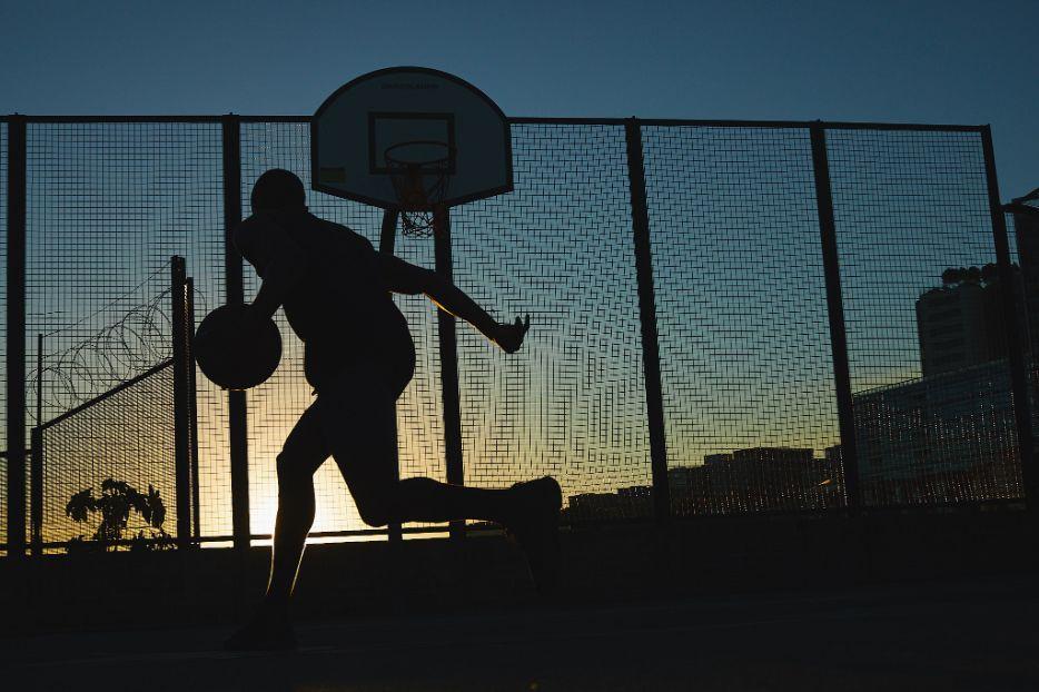 Daren L playing basketball at dusk