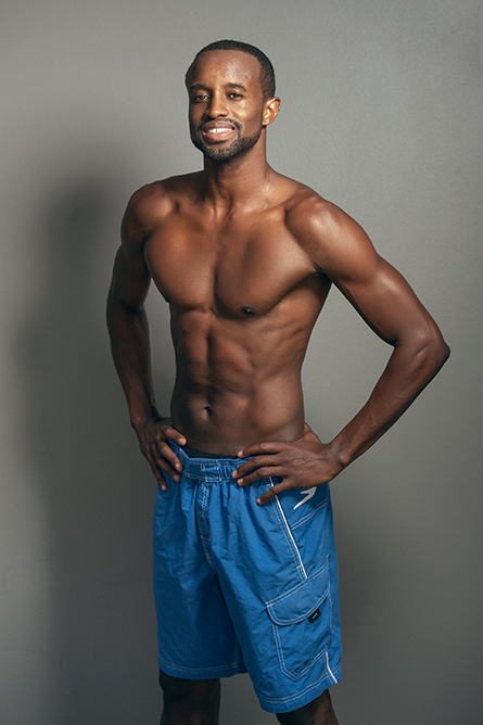Darren L standing topless wearing blue fitness shorts