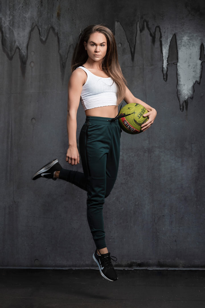 Georgia R jumping with a soccer ball under her left arm