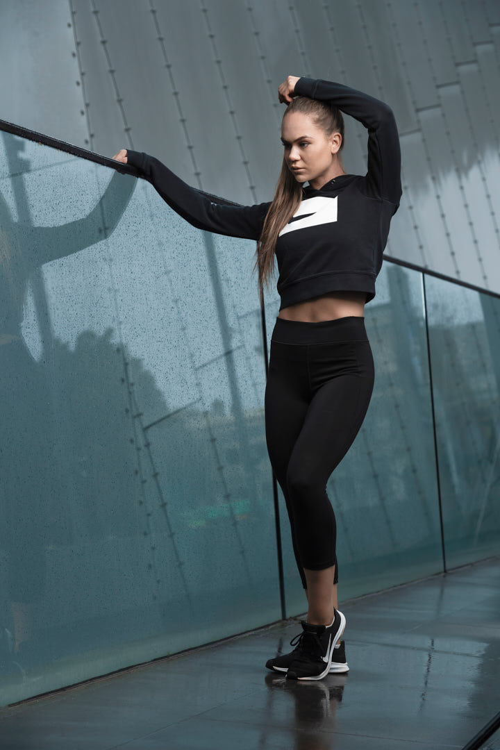 Georgia R standing in front of high reflective glass wearing a Nike black hooded top