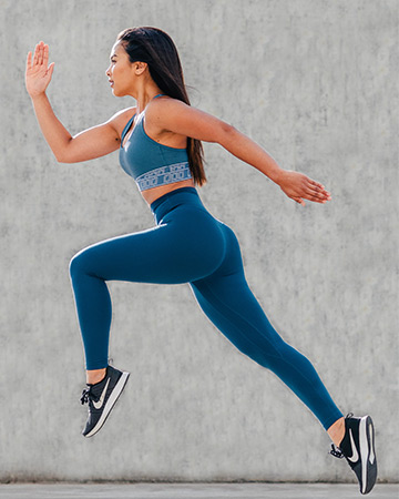 Gladysha bounding in blue sportswear against a concrete background