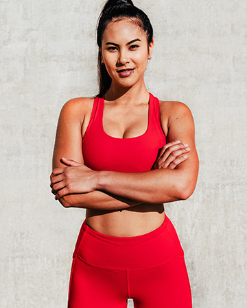 Gladysha folding both arms whilst wearing red fitted leggings and red crop top
