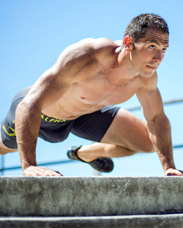 Harry Sydney male fitness model performing a Spiderman crawl