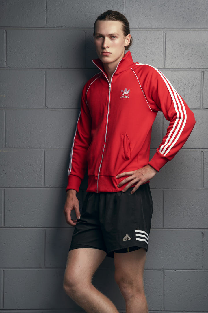 Jacob standing against a grey wall wearing original red Adidas tracksuit top