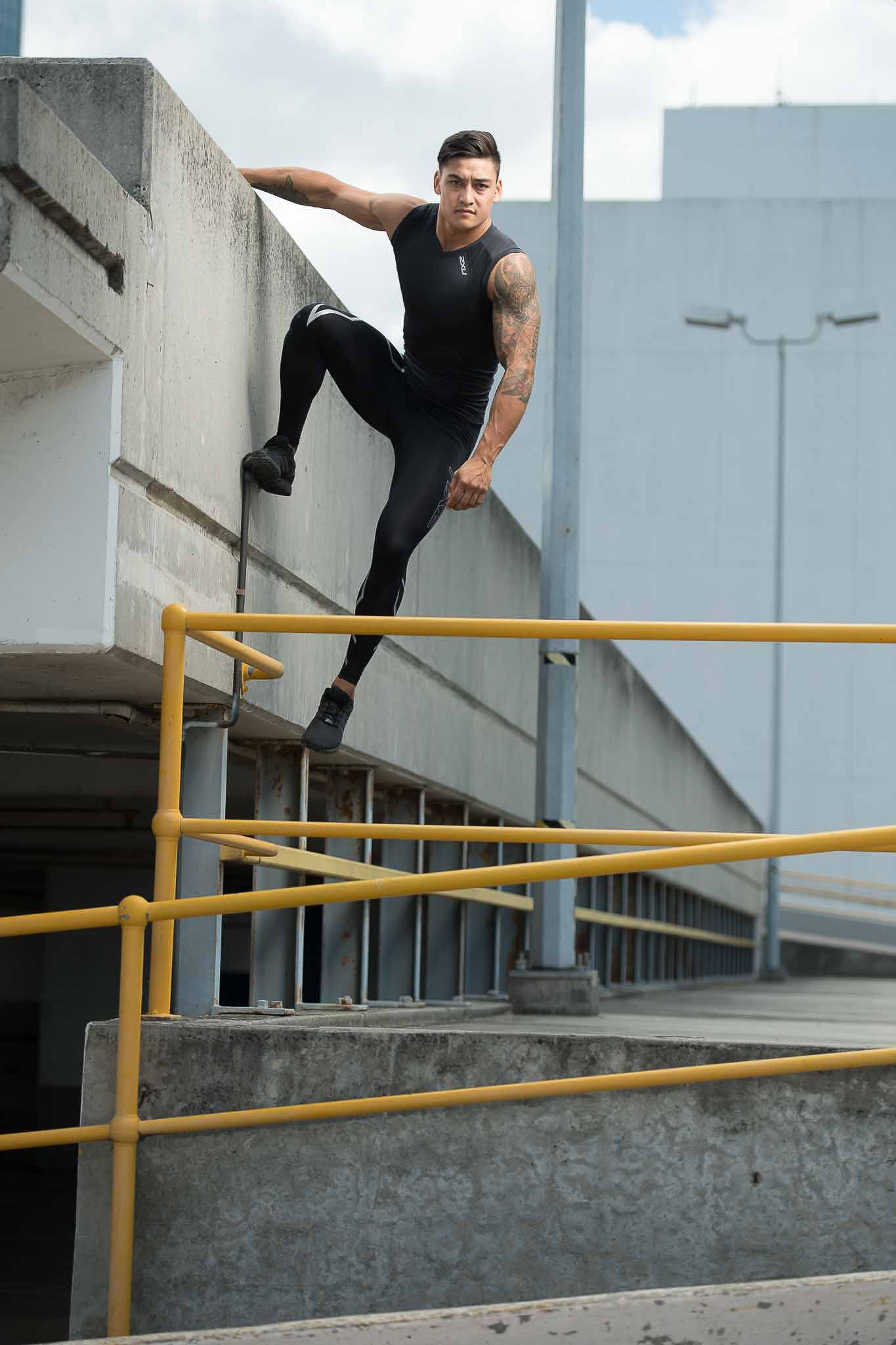 James hanging off the side of a carpark roof