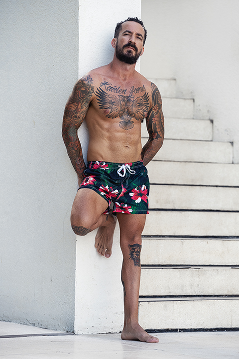 James standing in swimming shorts against a white wall