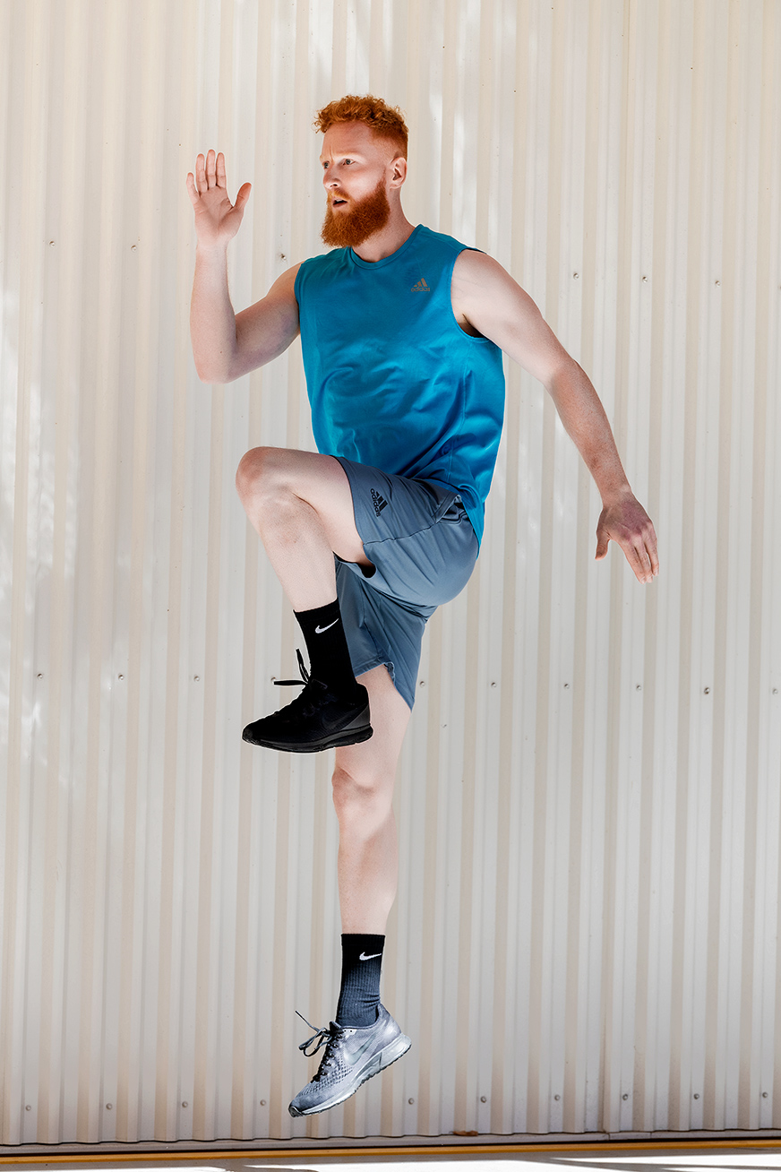 Jared jumping against a corrugated metal backdrop